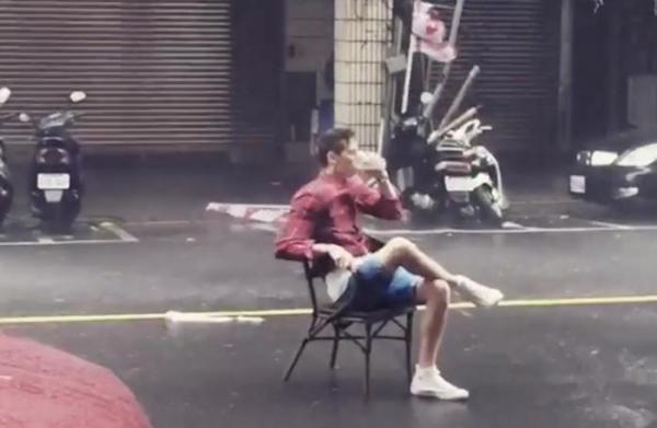 Thản nhiên đọc báo, uống trà trong siêu bão giữa đường phố - 1