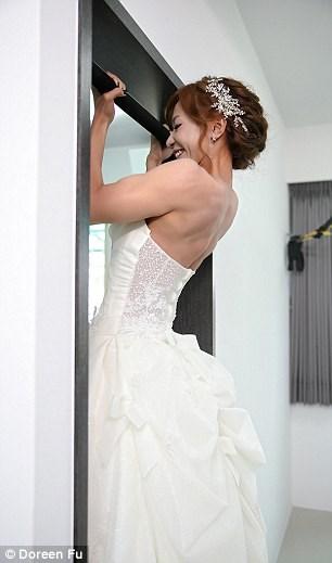 Cô dâu mặc váy cưới đu xà khoe cơ bắp cuồn cuộn - 1