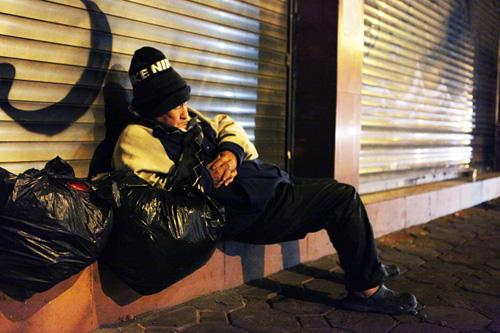 Người vô gia cư mặc áo mưa chống rét, ngủ trên vỉa hè - 6