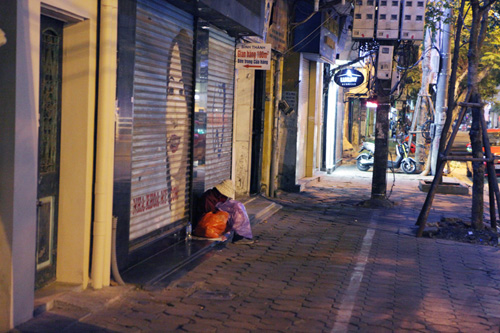 Người vô gia cư mặc áo mưa chống rét, ngủ trên vỉa hè - 1