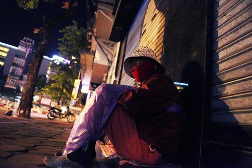 Người vô gia cư mặc áo mưa chống rét, ngủ trên vỉa hè - 2