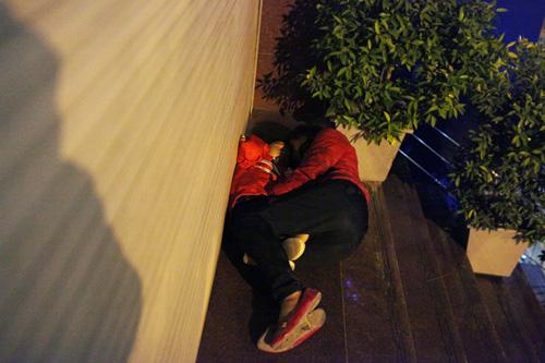 Người vô gia cư mặc áo mưa chống rét, ngủ trên vỉa hè - 4