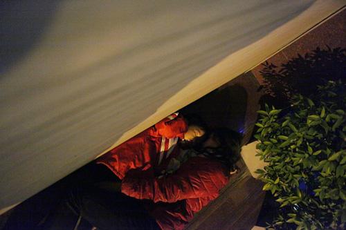 Người vô gia cư mặc áo mưa chống rét, ngủ trên vỉa hè - 5