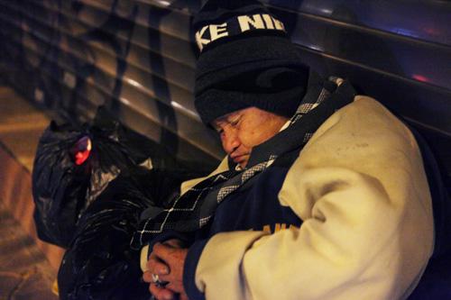 Người vô gia cư mặc áo mưa chống rét, ngủ trên vỉa hè - 7