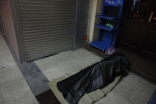 Người vô gia cư mặc áo mưa chống rét, ngủ trên vỉa hè - 12