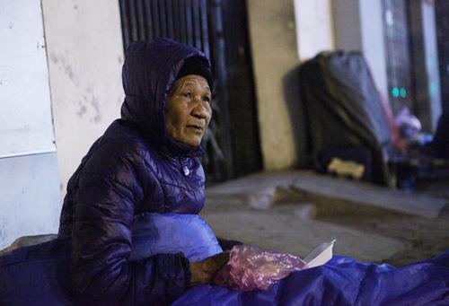 Người vô gia cư mặc áo mưa chống rét, ngủ trên vỉa hè - 11