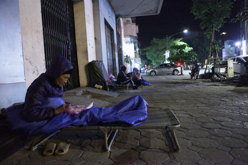 Người vô gia cư mặc áo mưa chống rét, ngủ trên vỉa hè - 10