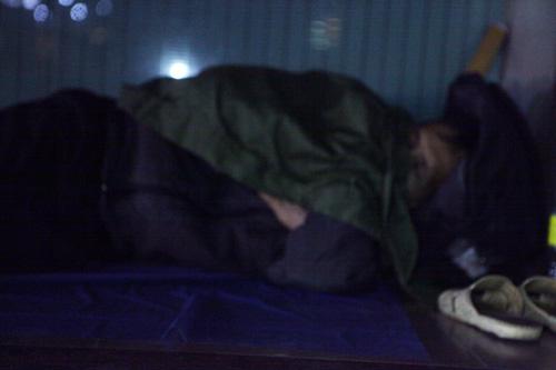 Người vô gia cư mặc áo mưa chống rét, ngủ trên vỉa hè - 8