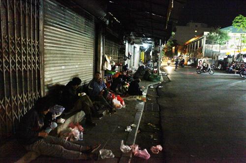Người vô gia cư mặc áo mưa chống rét, ngủ trên vỉa hè - 13
