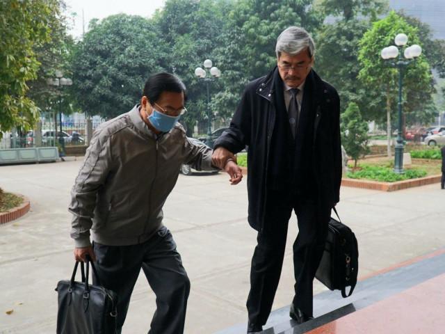 Cựu Bộ trưởng Vũ Huy Hoàng vịn cầu thang, nắm tay luật sư khi bước lên bậc thềm tòa án