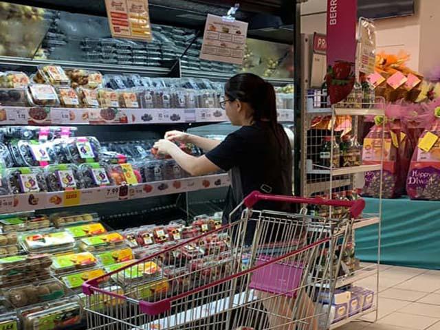Coi siêu thị như chợ, cô gái thản nhiên bóc từng hộp dâu để lựa quả ngon nhất