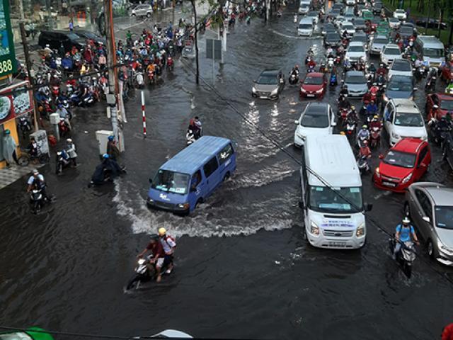 """Đường phố Sài Gòn ngập lênh láng sau cơn mưa lớn, người dân """"bơi"""" trong nước đen ngòm để về nhà"""