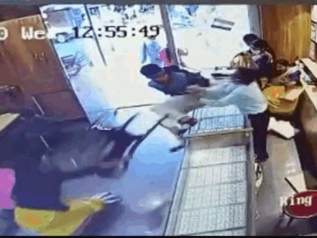 Xông vào cướp tiệm vàng, nam thanh niên bị cô gái phang thẳng ghế vào mặt
