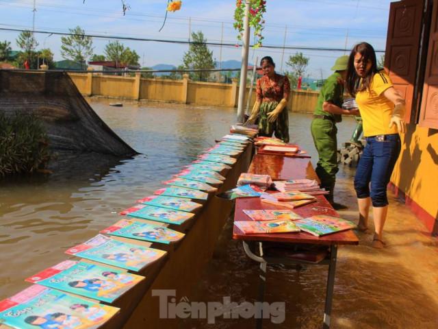 Lũ rút, giáo viên lội nước cao nửa mét vào trường mò tìm sách cho trò