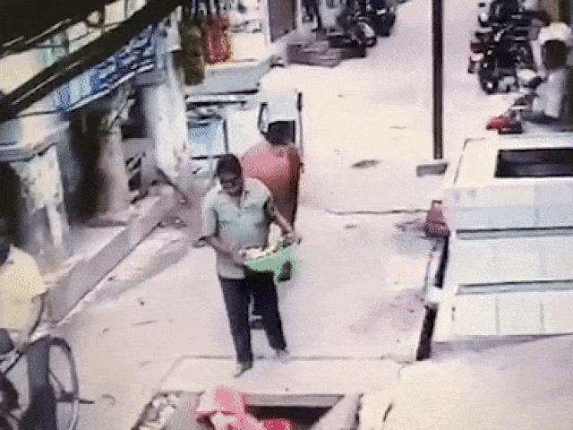 Đang đi trên đường, người đàn ông bị bò hất xuống cống