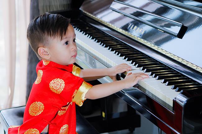 Cậu nhóc Jacky cực xinh trai khi tạo dáng bên chiếc đàn piano của mẹ Thảo.