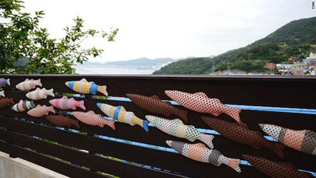 Những chú cá ngang dọc trên tường không chỉ để trang trí mà là một cách dân làng nghĩ ra để giúp những vị khách phương xa tránh bị lạc đường. Trên từng chú cá là những chấm người nhỏ xíu đang cưỡi lên những chú cá lướt theo sóng, hay đang tinh nghịch sờ vào vảy cá. Chiều chiều, dưới cái ánh nắng vàng của Busan, người dân lại kê phản ra ngồi uống trà, rì rầm trò chuyện bên cạnh những hũ tương, hũ kim chi trên nóc nhà.
