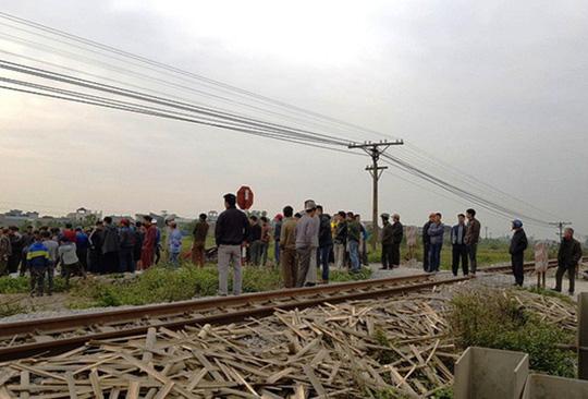 Tàu hỏa tông 2 người đi xe máy văng xuống ruộng tử vong - 1