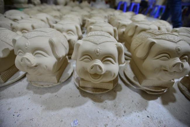 """Gần Tết Nguyên đán, những chú lợn đất dát vàng mang tên """"Kỳ linh Kỷ Hợi"""" được bày bán tại làng gốm Bát Tràng, Hà Nội."""