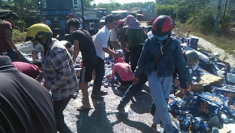 Người dân giúp tài xế gom hàng trăm thùng bia đổ ra đường - 1