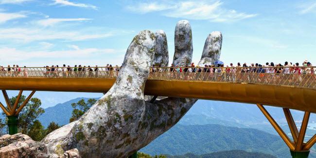 """Cầu Vàng, Việt Nam: Cây cầu nằm trong khu vườn Thiên Thai thuộc Khu du lịch Bà Nà Hills, Đà Nẵng. Mặt cầu có chiều dài 150m và được nâng bởi hai bàn tay khổng lồ ở độ cao 1.400 so với mặt nước biển. """"Đôi bàn tay"""" trông như có niên đại nhiều thế kỷ, nhưng chúng mới được xây dựng vào năm 2018."""
