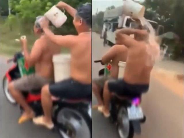 Video hai người đàn ông Việt tắm gội trên xe máy lên báo ngoại