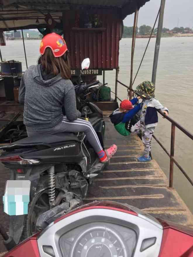 Hai đứa trẻ đánh đu vắt vẻo ngoài thành phà qua sông, thái độ của bà mẹ khiến tất cả bức xúc - 1