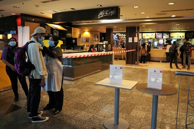 Nhân viên tại cửa hàng McDonald kiểm tra thân nhiệt của khách trước khi vào.