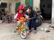 Mong ước trong năm mới của ông bố ôm con đi bán bọc chân chống xe máy