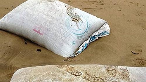 Cả trăm bao tải chứa chất lạ in chữ TQ dạt vào biển - 1