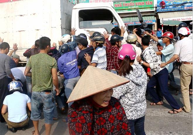 Hàng chục người dân nhấc xe tải, cứu 2 người đàn ông - 1