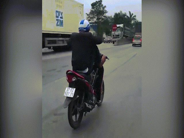 Nam thanh niên dùng 2 chân điều khiển xe máy, tay cầm điện thoại trên quốc lộ