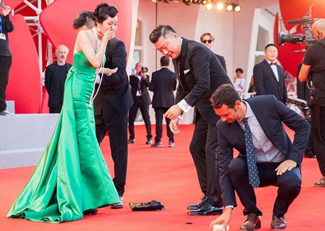 Chiếc túi xách của nữ diễn viên văng ra thảm đỏ, rơi luôn bình sữa trong túi khiến nhân viên an ninh tại LHP Venice phải nhặt lại.