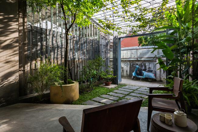 Các kiến trúc sư sử dụng kệ sắt như một vách ngăn giữa phòng khách và mái hiên nhưng vẫn đảm bảo được việc thông gió.