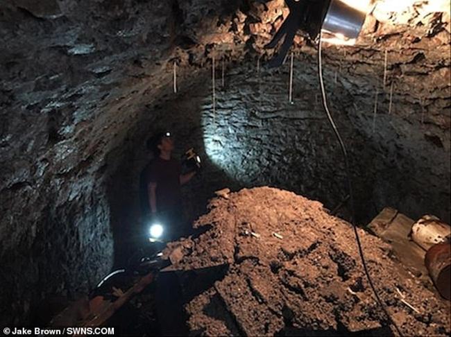 Sau khi khoan, Jake nhìn qua lỗ khoan xuống dưới. Người đàn ông này tìm thấy một đường hầm có từ năm 1900.