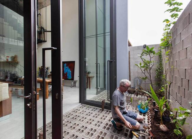 Được ngăn cách bởi phòng khách và cầu thang trung tâm của ngôi nhà, phía sau tòa nhà được thiết kế với một nhà bếp và khu vực ăn uống tiện nghi, có thể mở ra phía trước một bức tường xanh ở phía sau.