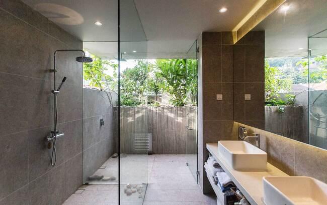 Phòng tắm rộng lớn, hiện đại với những tấm kính lớn gần những bụi cây xanh.