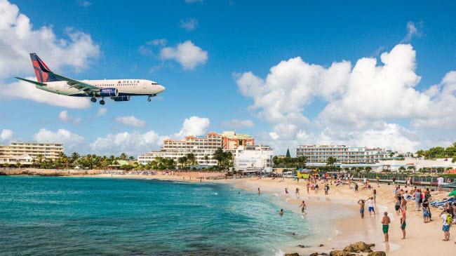 Maho, St Maarten: Bãi biển này nằm ngay sát sân bay quốc tế Princess Juliana, nên du khách có thể vừa tắm biển vừa quan sát những chiếc máy bay khổng lồ lướt qua đầu họ.