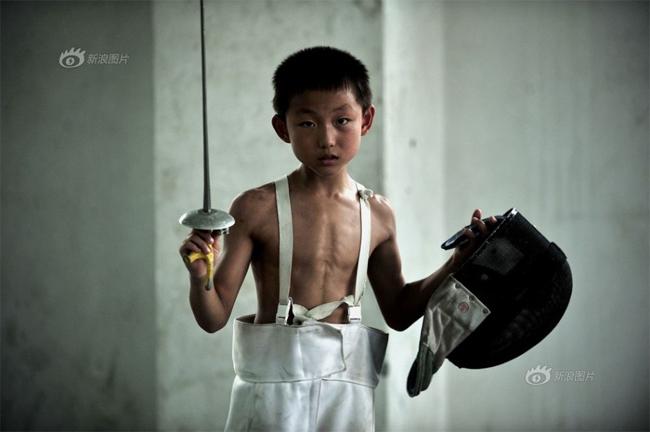 Một vận động viên đấu kiếm nhí trong trang phục của các đàn anh. Có lẽ người ta còn chưa sản xuất những bộ đồ thi đấu môn đấu kiếm dành cho những em nhỏ như vậy.