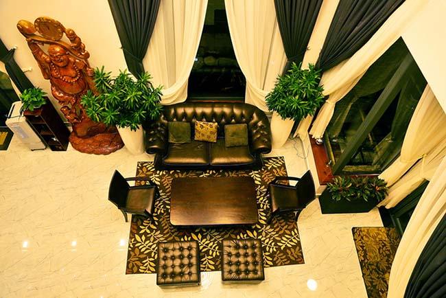 Phòng tiếp khách với ghế sofa tối màu. Rèm cửa gây ấn tượng với chiều dài hơn 3m.