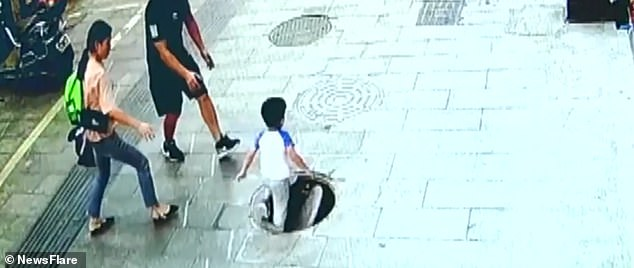 Video: Bé trai 3 tuổi đang đi bộ trên đường, vài giây sau rơi xuống hố sâu - 1
