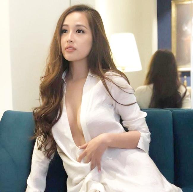 Người đẹp diện một chiếc sơ mi trắng dáng dài, buông nhiều hàng cúc để lộ vòng một lấp ló sau lớp vải mỏng.