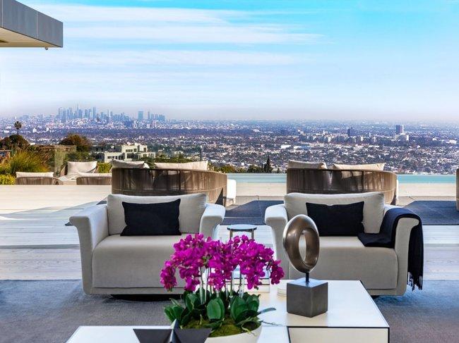 Trong phòng khách, một bức tường kính có thể thu vào mở ra để giúp tầm nhìn ra toàn bộ thành phố không bị che khuất.