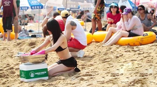 Một cô gái trẻ mặc bikini muối kimchi  giữa bãi biển ở Haeundae, Pusan, Hàn Quốc.