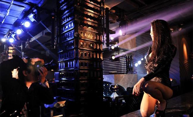 Một góc hình khác, người mẫu nửa ngồi nửa quỳ trên bục để ống kính tác nghiệp.