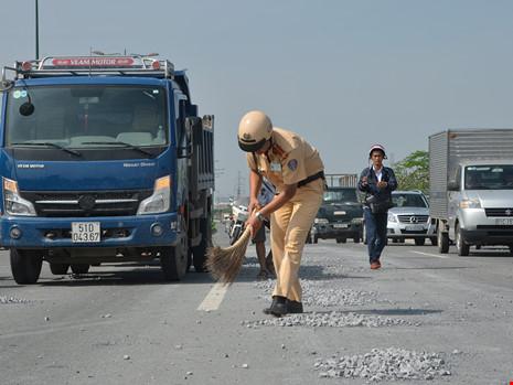 Cảnh sát giao thông đội nắng dọn đá rơi trên đại lộ - 1