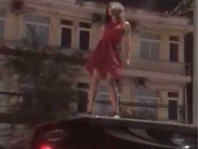 Sốc với cô gái mặc váy đỏ trèo lên nóc ô tô nhảy múa, lăn lộn