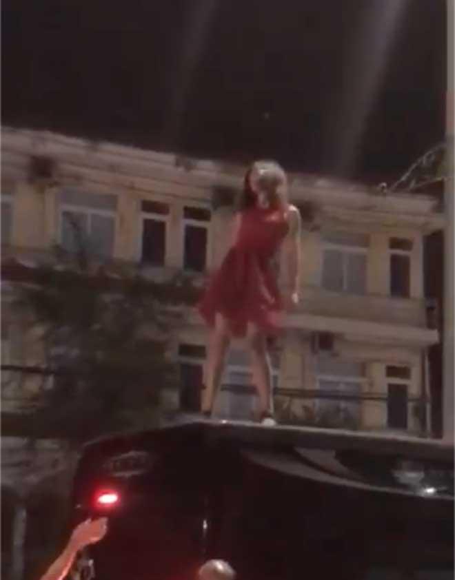 Sốc với cô gái mặc váy đỏ trèo lên nóc ô tô nhảy múa, lăn lộn - 1