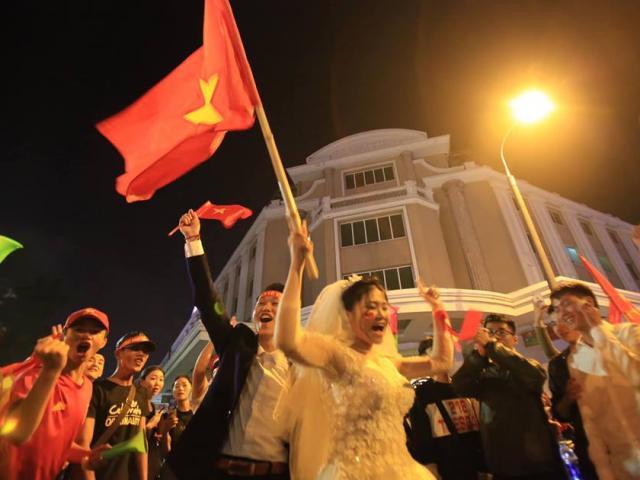 """Cô dâu chú rể dừng """"nhiệm vụ"""", phất cờ ăn mừng theo đoàn CĐV"""