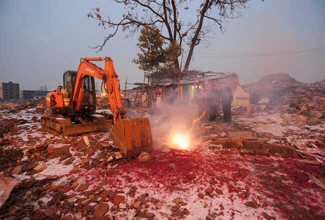 """Cao Wenxia, chủ sở hữu của """"ngôi nhà đinh"""" này ở Hợp Phì, đốt pháo để chúc mừng năm mới của Trung Quốc. Ngay trước mặt họ là một chiếc máy ủi được sử dụng để phá hủy các tòa nhà xung quanh."""